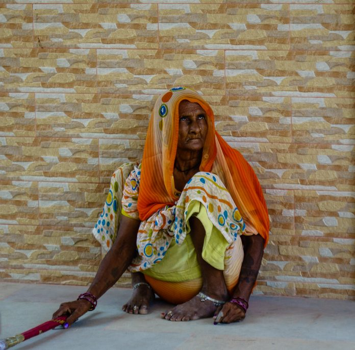 An old woman in India sweeping floor to make money